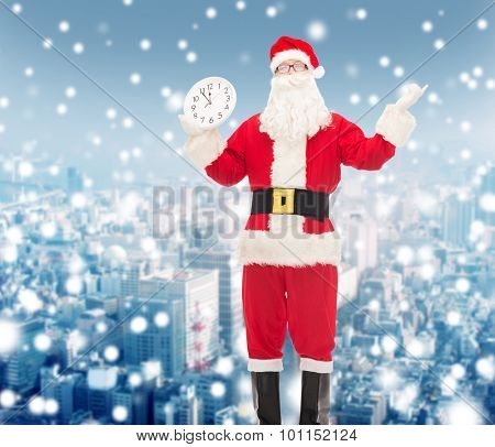 christmas, holidays and people concept - man in costume of santa claus with clock showing twelve over snowy city background