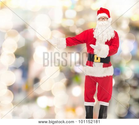 christmas, holidays, gesture and people concept - man in costume of santa claus over lights background