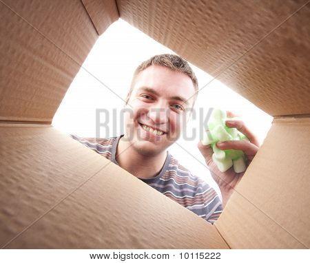 Homem jogando Polyfoam embalagem em caixa de papelão