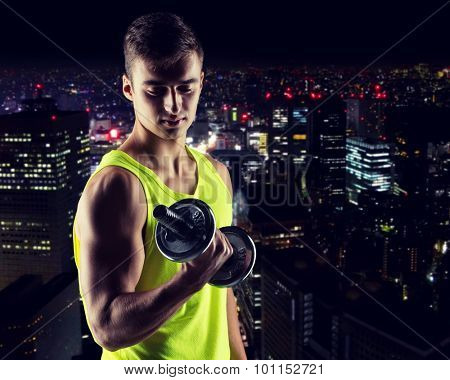 sport, bodybuilding, training and people concept - young man with dumbbell flexing biceps over night city background