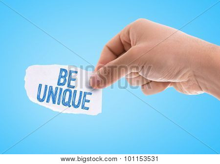 Piece of paper with the word Be Unique with blue background