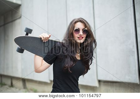 Stylish teenager girl with a longboard
