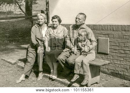 Vintage photo of family sitting on bench, 1950's