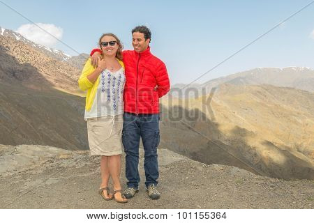 Inter ethnic couple of tourists posing on Tizi-n-Tichka pass, High Atlas mountains, Morocco