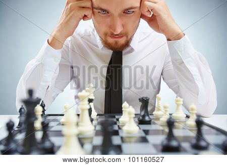 Pensive businessman leaning over chessboard