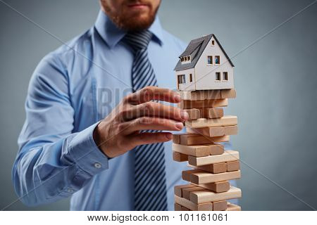 Businessman taking out wooden block from tower with house model on its top