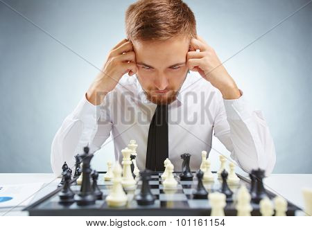Pensive businessman in formalwear looking at chessboard while leaning over it