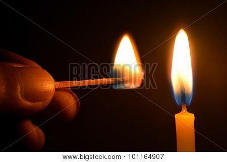 Holding Matches and candle fire on black background
