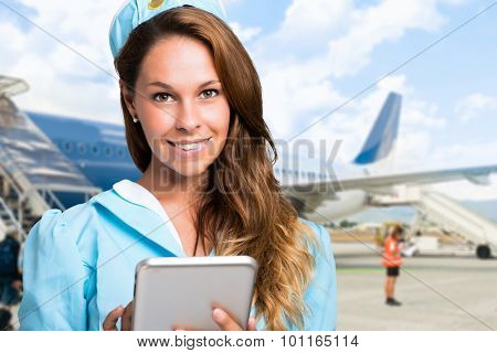 Portrait of a smiling stewardess using a tablet in front of an airplane