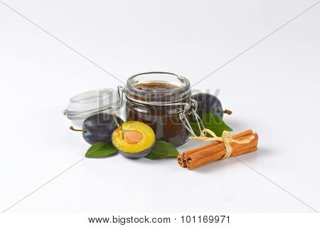 jar of fresh plum jam, ripe plums and cinnamon on white background