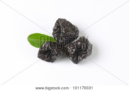dried plums and plum leaf on white background