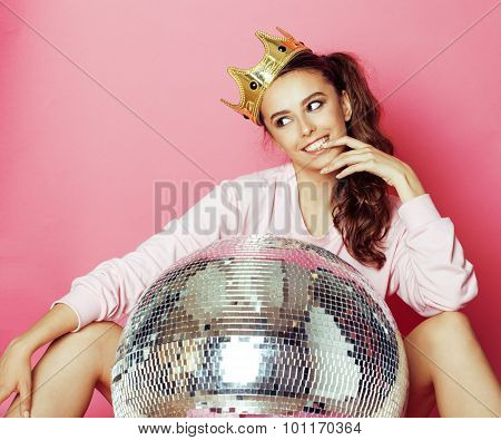 young cute disco girl like doll on pink background with disco ball and crown