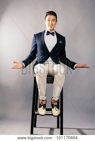 young handsoman businessman fooling aroung with chair in studio