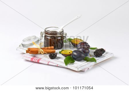 plum jam, cinnamon, fresh and dried plums on wooden cutting board