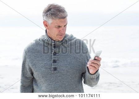 Smiling man standing and on his phone at the beach