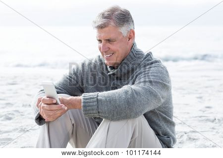 Smiling man sitting and on his phone at the beach