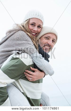 Smiling man giving his partner a piggy back at the beach