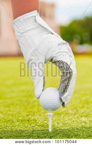Hand In A White Glove Puts The Golf Ball On A Tee