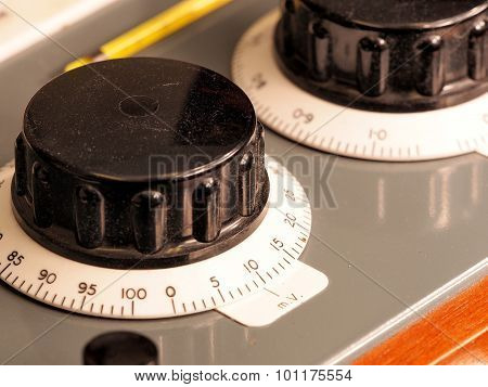 Big black hand knobs with rotating scale on an old test apparatus