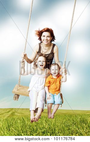 Family fun. Mom, daughter, son laughing on a swing against the sky and clouds. Family weekend vacation.