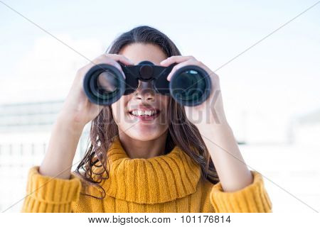Pretty woman looking through binoculars outside