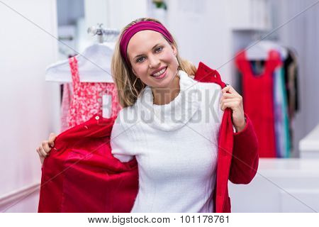 Portrait of smiling woman putting on red coat in clothing store