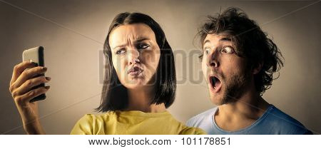 Shocked couple reading something on a phone