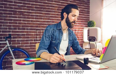 Businessman writing on graphic tablet while using laptop in creative office