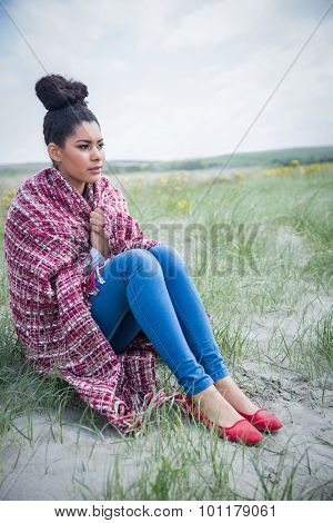 Beautiful woman wrapped up in warm clothing at the beach