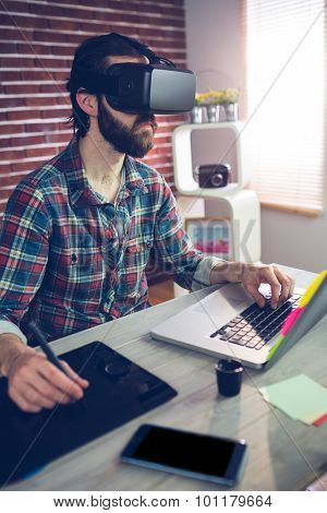 Focused creative businessman using 3D video glasses with laptop and graphic tablet at ofice