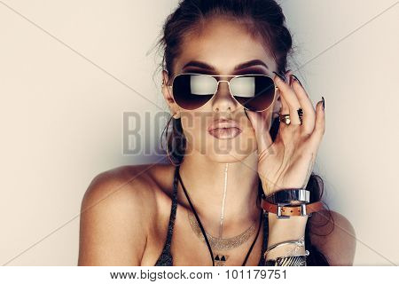 Glamorous young woman with flash tattoos in sunglasses