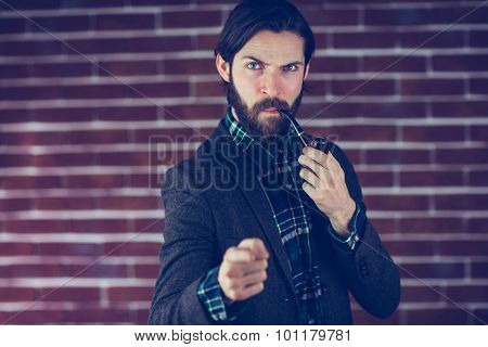 Portrait of serious man with smoking pipe pointing finger against brick wall