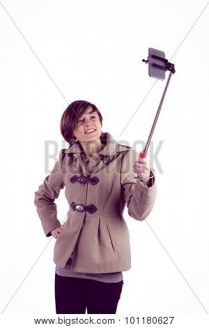Attractive woman taking a selfie with a selfie stick