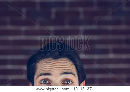 Portrait of man with raised eyebrows against brick wall