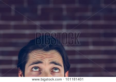 Confused man with raised eyebrows against brick wall