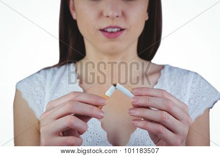 Woman snapping cigarette in half on white background