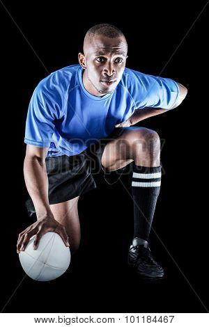 Serious rugby player kneeling while holding ball against black background