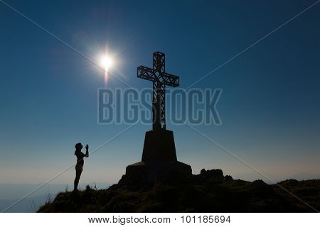 Girl Prays In Front Of The Mountain To The Summit Cross
