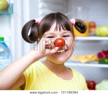 Girl Eating Tomatoes Standing Near Refrigerator