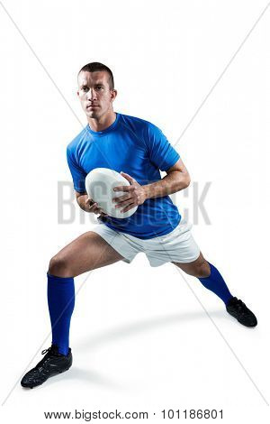 Full length of rugby player exercising with ball against white background