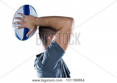 Profile view of rugby player throwing ball against white background