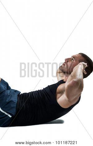 Confident athlete doing tummy crunches against white black