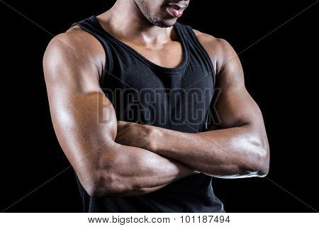 Mid section of muscular man with arms crossed standing against black background