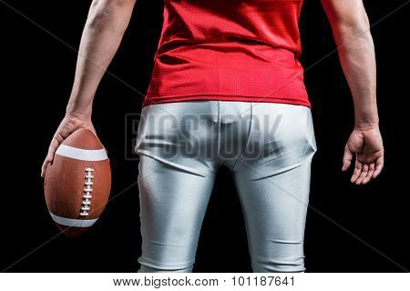 Mid section of sportsman with American football standing against black background
