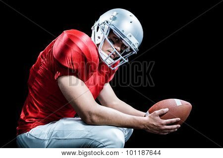Portrait of American football player crouching while holding ball against black background