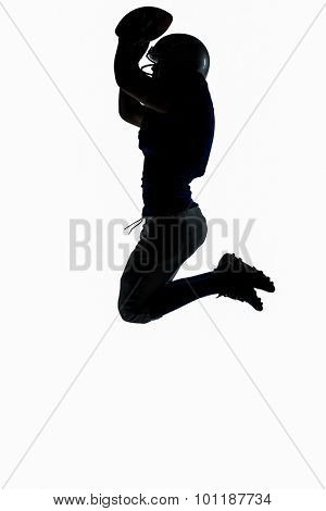 Side view of silhouette American football player jumping while holding ball against white background