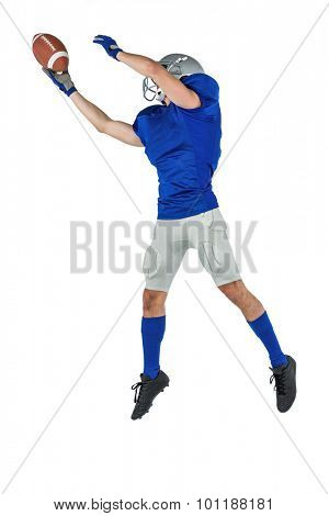 Full length of sports player catching ball in mid-air against white background