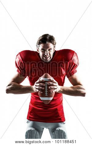 Portrait of furious American football player in red jersey holding ball on white background