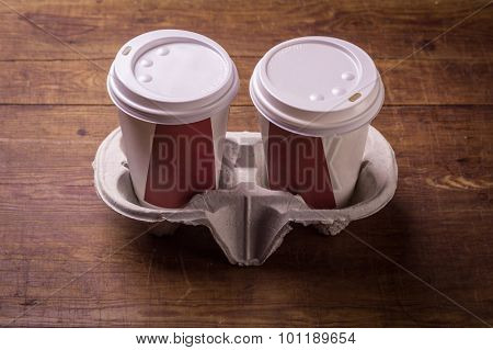 Paper cups of coffee on wood background.