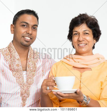 Portrait of happy Indian family at home. Mature 50s Indian mother and 30s grown son.